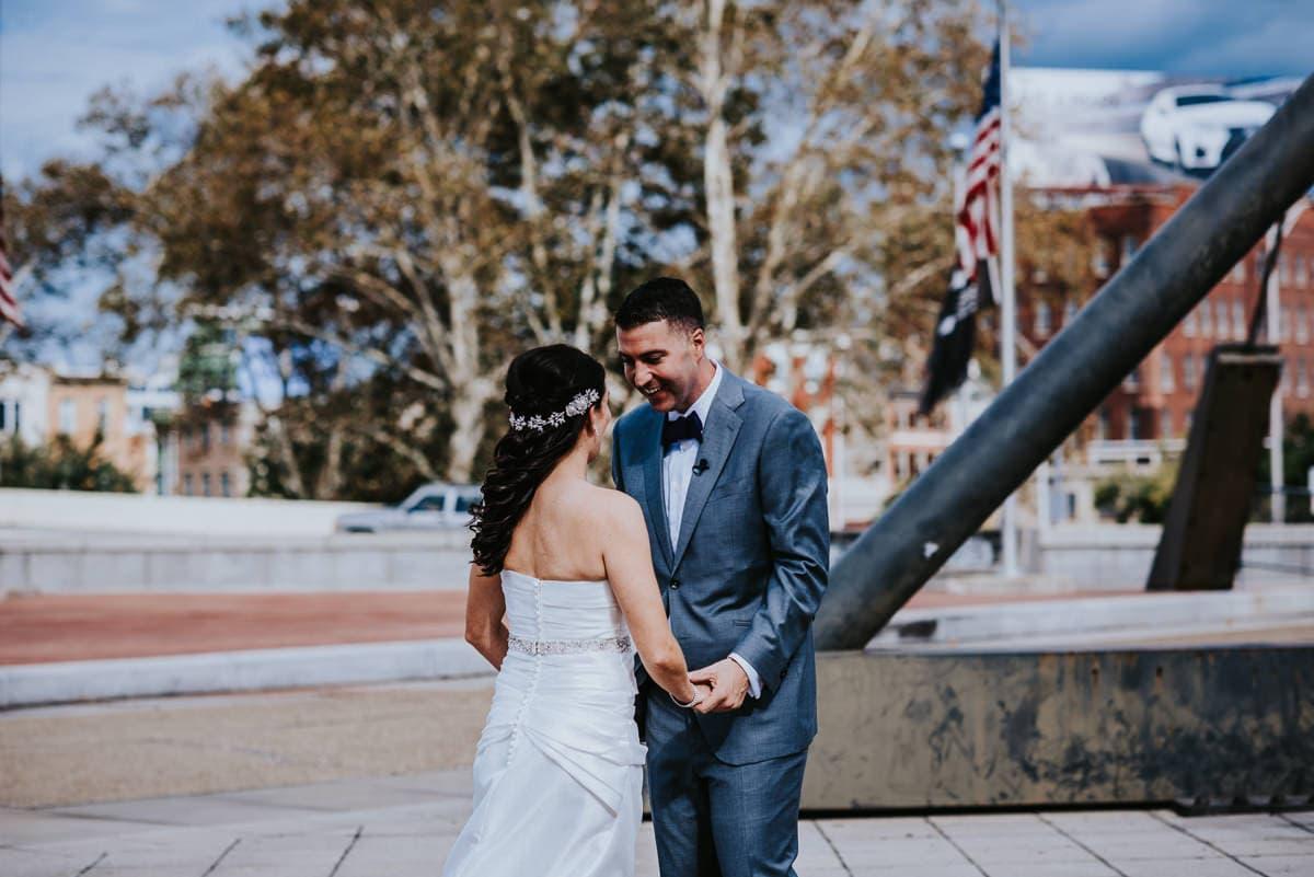 groom admiring brides dress